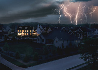 A single home with electric power supplied by a home generator during an outage. Lightning in the background