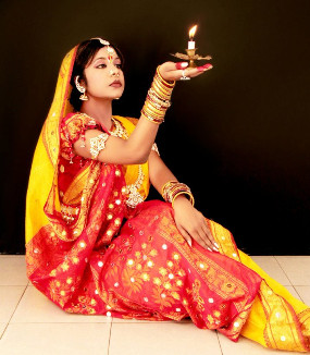 Image of Shipra Parish sitting on the floor holding a candle in the palm of her hand.